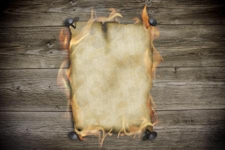 burning paper: Burning old paper on wood background