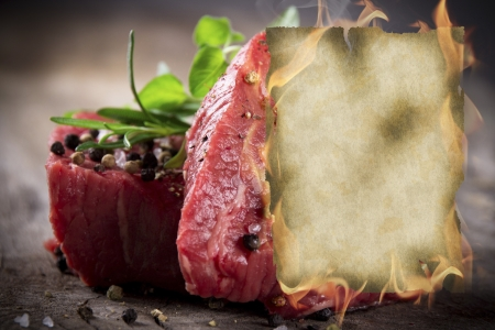 Raw beef steaks with burning blank paper photo