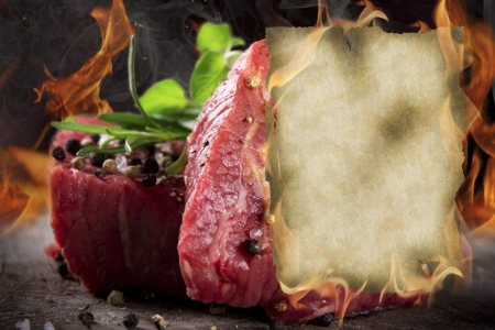 fillet steak: Raw beef steaks with burning blank paper Stock Photo