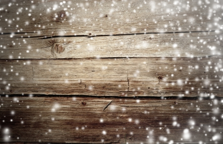 Old wooden background with falling snow flakes photo