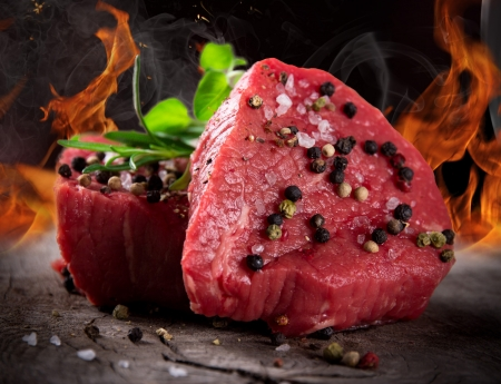 Raw beef steaks with fire flames photo