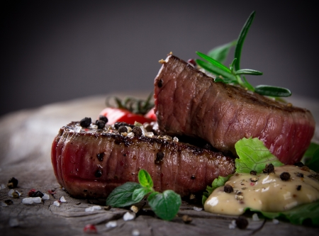 medium close up: Medium grilled bbq steaks with fresh herbs and tomatoes