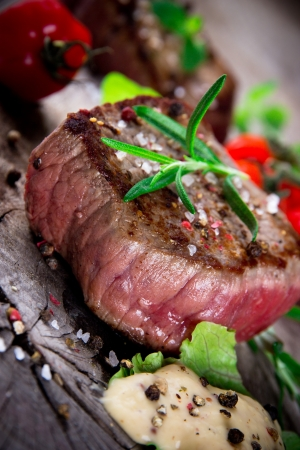 Bloody bbq steak with fresh herbs and tomatoes Stock Photo - 16308902