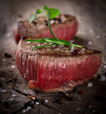 medium close up: Grilled bbq steaks on wooden background