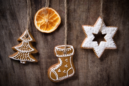Traditional gingerbread cookies hanging over wooden background photo