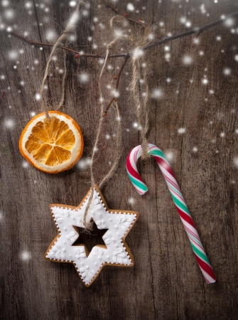 Christmas sweets hanging over wooden background photo