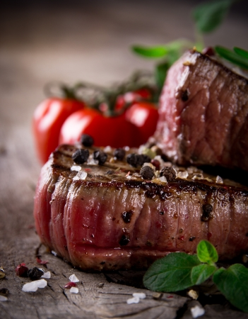 beef cuts: Medium grilled bbq steaks with fresh herbs and tomatoes