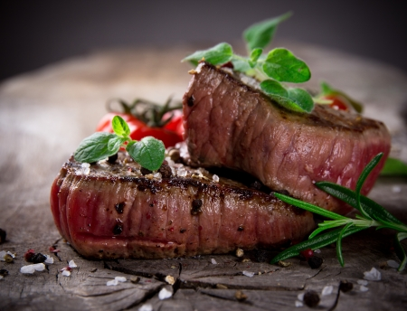 restaurant food: Grilled bbq steaks with fresh herbs and tomatoes