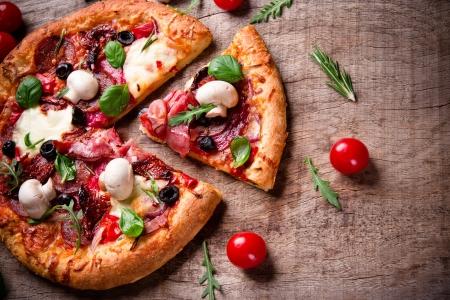 pizza: Deliciosa pizza italiana servida en mesa de madera