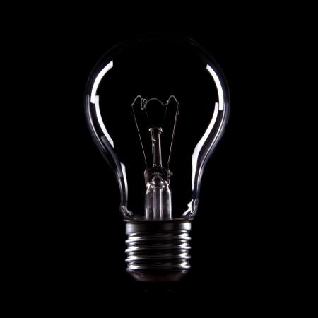 brilliant idea: Light bulb on black background Stock Photo