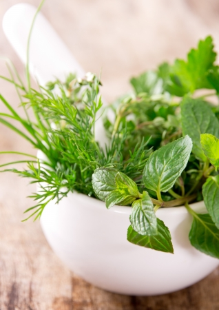 Mortar with herbs on wooden table photo
