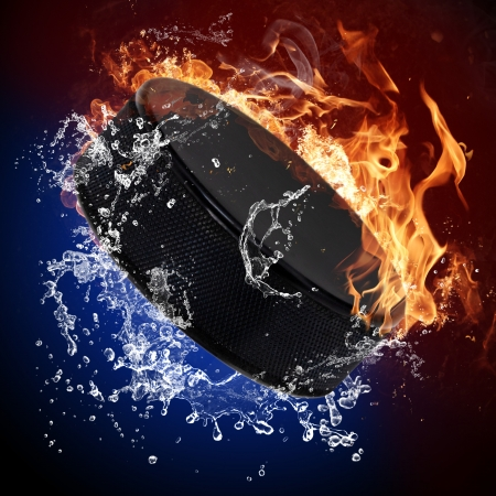 extreme heat: Hockey puck in fire flames and splashing water Stock Photo