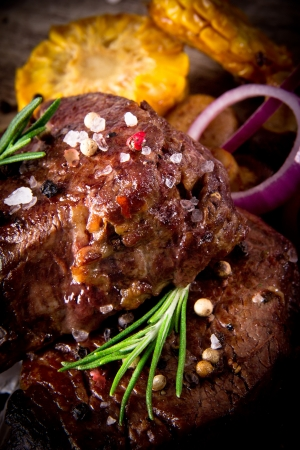 Delicious beef steaks on wooden table Stock Photo - 19859622