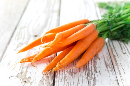 Fresh carrots on wooden background photo
