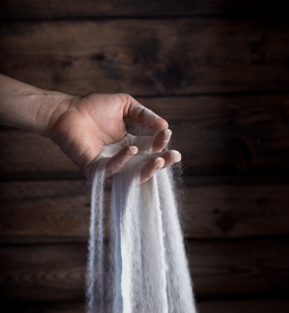 trickle down: sand running through hands as a symbol for time running Stock Photo