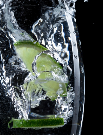 Cocktail with ice and lime slice isolated on black background photo