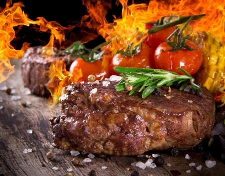 barbecue: Delicious beef steak on wooden table with fire flames Stock Photo