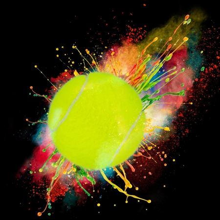 Colorful paint splashing with tennis ball isolated on black photo
