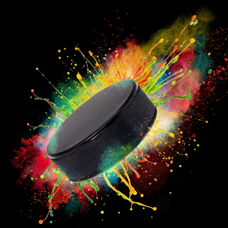 Colorful paint splashing with hockey puckl isolated on black photo