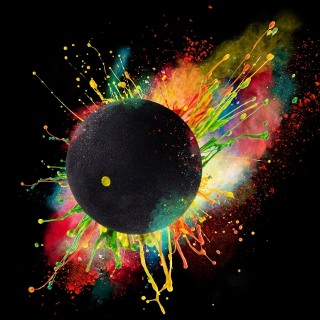 Colorful paint splashing with squash ball isolated on black Фото со стока
