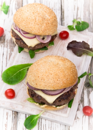 Delicious hamburgers on wooden background photo
