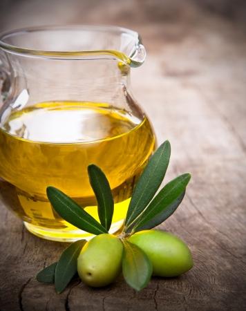 hoja de olivo: Aceitunas con hojas sobre un fondo de madera
