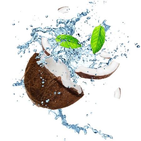 spruzzi acqua: Noce di cocco con spruzzi d'acqua su bianco Archivio Fotografico