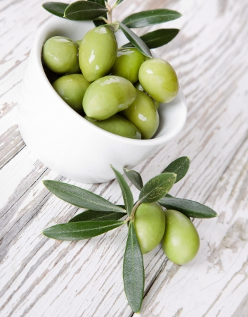 green life: Olives with leaves on a wooden background  Stock Photo