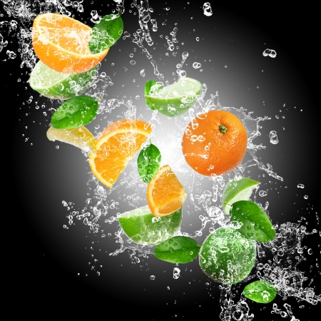 solid food: Oranges with water splash isolated on a dark background Stock Photo