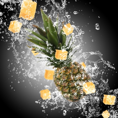 Pineapple with water splash over dark background photo