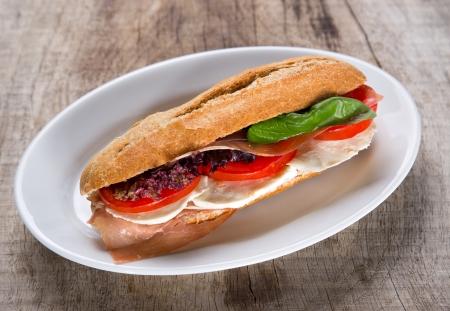 sandwiche: Ham salad baguette on rustic table
