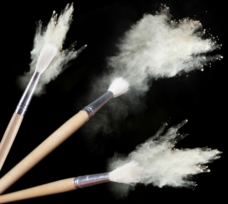 make up artist: Make up brushes with powder isolated on black
