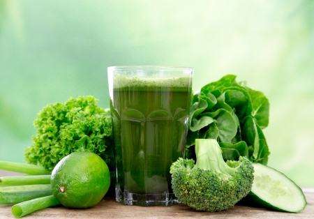 Healthy green vegetable juice on wooden table photo