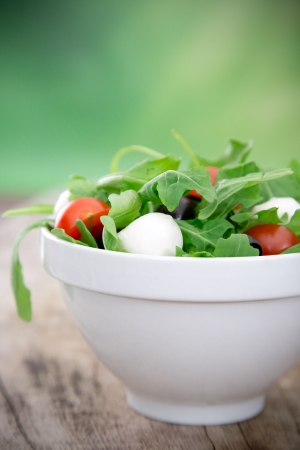 Fresh salad over wooden background photo