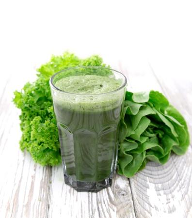 espinacas: Jugo vegetal verde sana en la mesa de madera