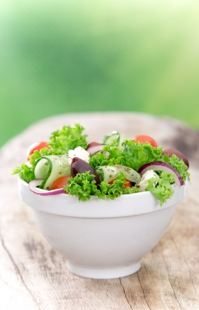 Fresh vegetable salad over wooden background photo