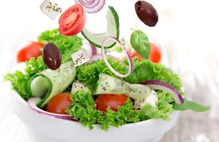 greek salad: Fresh vegetable salad over wooden background Stock Photo