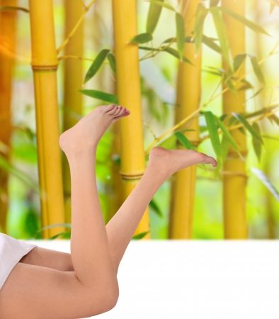 Beautiful long slim woman legs on bamboo background  photo