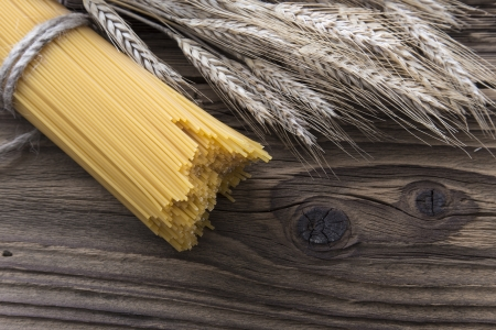 un cook: Bundle of long spaghetti on a old grungy wooden desk