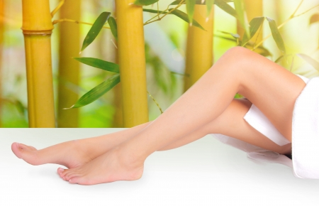 Beautiful long woman legs with bamboo background photo