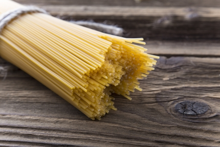 un cook: Bundle of long spaghetti on a old grungy wooden desk  Stock Photo