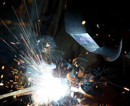 welder: Welder in action with bright sparks  Construction and manufacturing theme