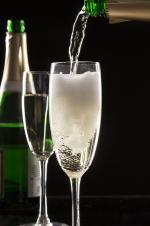 Pair of champagne flutes over black background