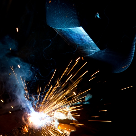Welder in action with bright sparks  Construction and manufacturing theme