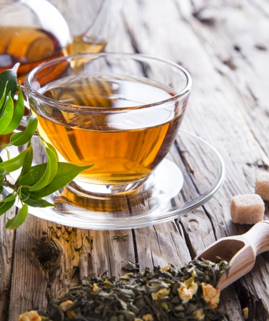 herbal tea: Transparent cup of green tea on wooden background