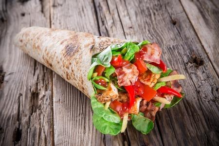 tortilla wrap: Rodajas de pollo en una envoltura de tortilla con lechuga en la madera