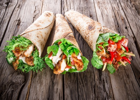 Chicken slices in a Tortilla Wrap with Lettuce on wood  photo