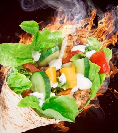 tortilla wrap: Rebanadas de pollo en una envoltura de tortilla con llamas de fuego