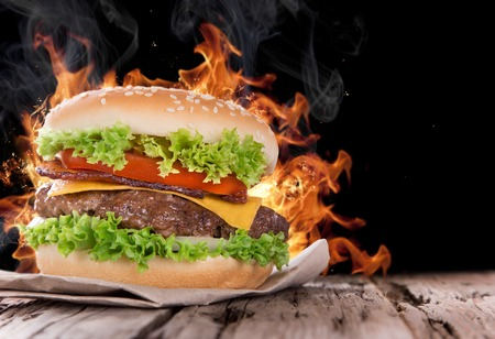 wood fire: Delicious hamburger with fire flames on wooden background