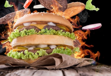 Delicious hamburger with fire flames on wooden background photo